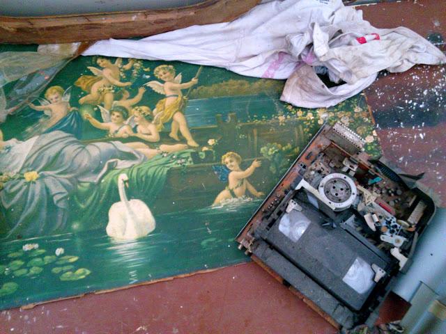Fotka z urbexu v domě s art brut výzdobou. Zobrazuje věci pohozené na zemi: starý obraz s andělíčky na zemi a na něm rozebraný videopřehrávač. (Autor: Sebastián Wortys)