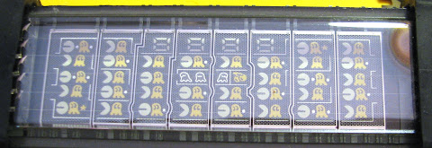 [Image: Close-up photo of the unlit display, revealing that it is a 8x5 grid of small pictures of the game characters and the scene, and a 7-segment, 4-character number display.]