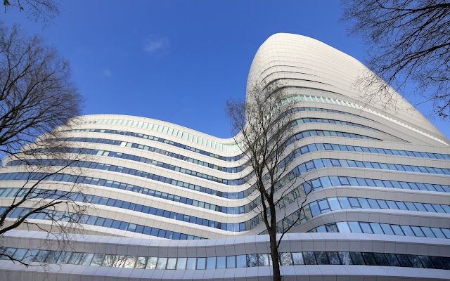 Picture of an office building during the day as seen from the entrance looking up