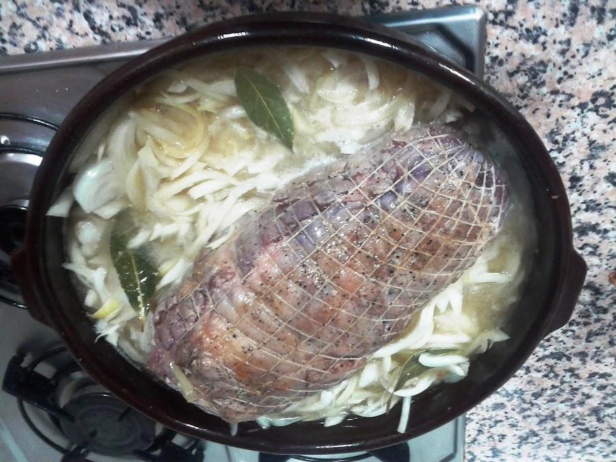 Cocinando el lomo relleno con la cebolla y el caldo.