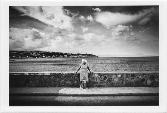 dirty photos - et - a black and white photo of old woman by the sea in rethymno
