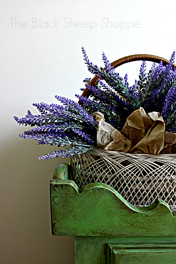 Basket filled with lavender on Antibes green dry sink cabinet.