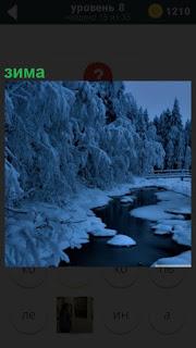 Деревья и ручей зимой покрылись снегом и льдом, но ручей не замерз