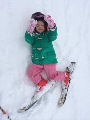 Niña tumbada sobre la nieve