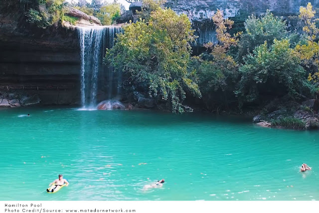 swimmers floating in front of the waterfall