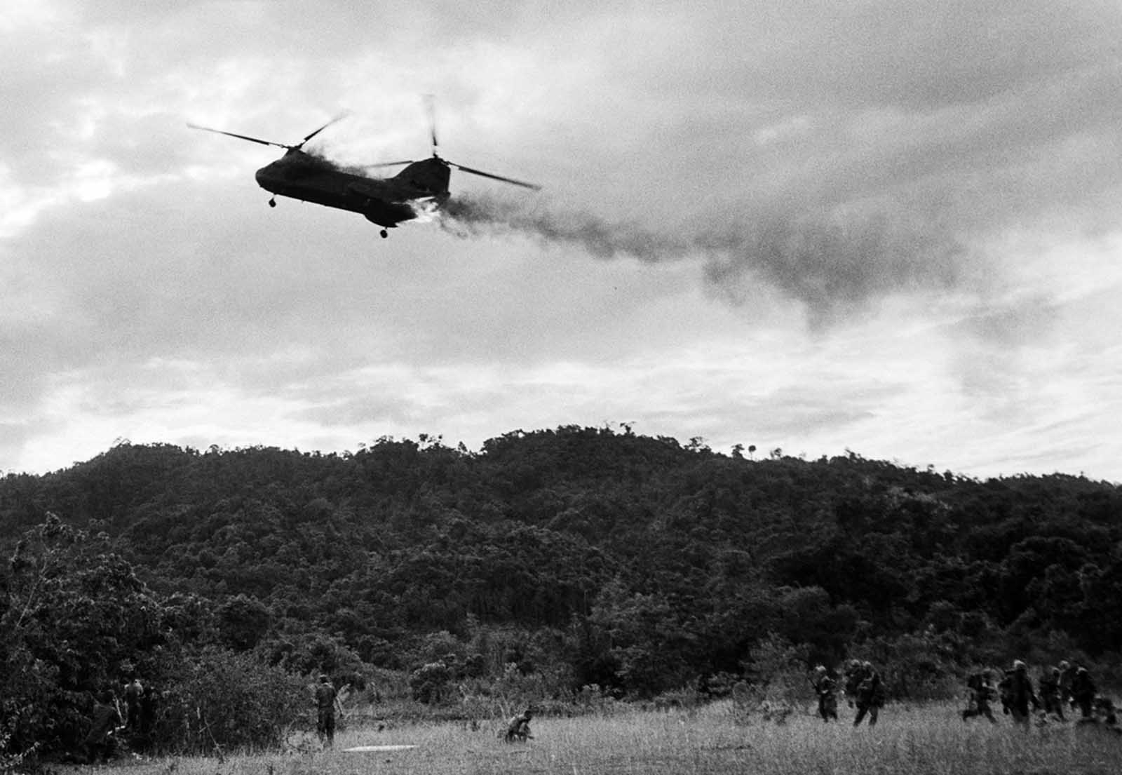 A U.S. Marine CH-46 Sea Knight helicopter comes down in flames after being hit by enemy ground fire during Operation Hastings, just south of the demilitarized zone between North and South Vietnam, on July 15, 1966. The helicopter crashed and exploded on a hill, killing one crewman and 12 Marines. Three crewmen escaped with serious burns.
