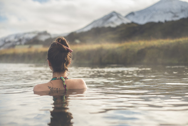 Girl swimming in a hot spring in Landmannalaugar during a romantic trip to Iceland