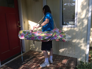Woman carrying folding chair in homemade flowered bag with strap.