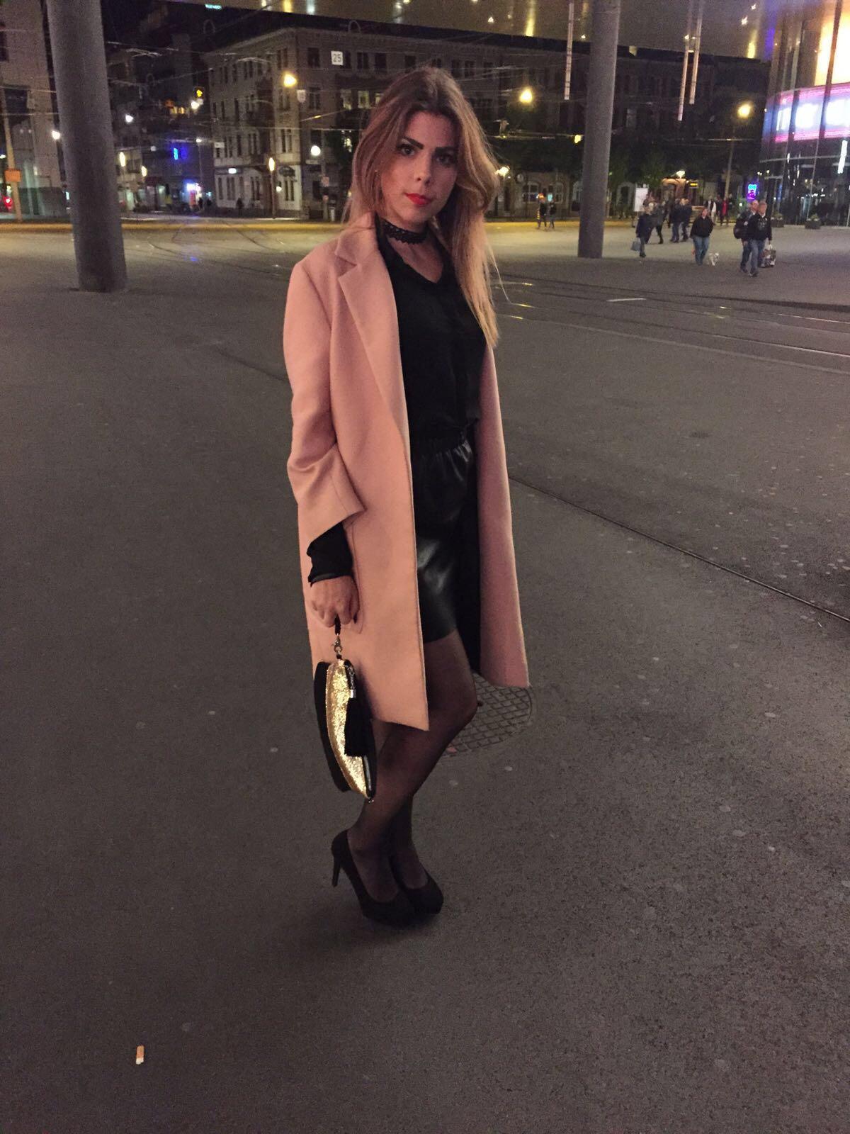 Lederjupe und pinker Mantel mit schwarzen Pumps