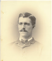 A portrait of a white man with well-combed hair and mustache, wearing a suit.