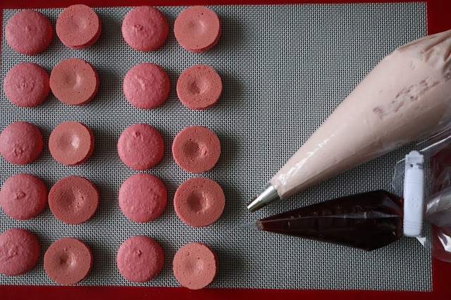 Pink Macaron Shells on a silicon mat with a piping bag filled with buttercream and another piping bag full of jelly.