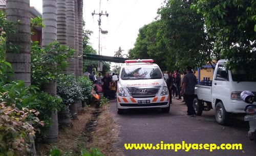 BERANGKAT : Sebuah ambulance tampak merapat di depan rumah duka.  Saya tidak tau apa maksud adanya mobil tersebut  Hujan sudah mulai turun saat itu. Foto Asep Haryono.