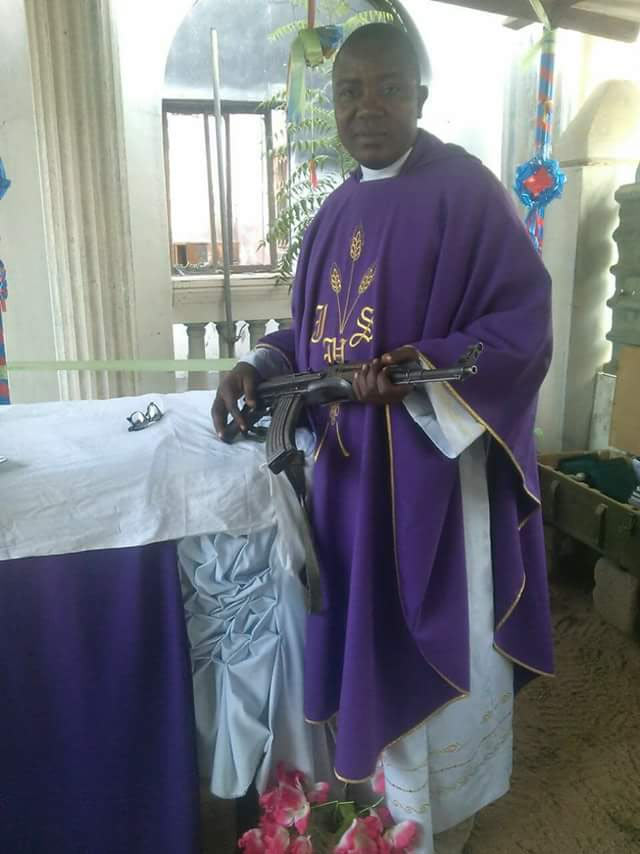 Catholic priest rocks AK-47 during mass