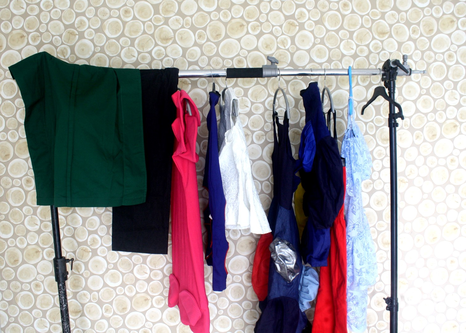A rack of clothes behind the scene of cassie daves mania magazine shoot.