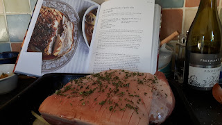 Pork joint ready for the oven with thyme and salt rubbed into the scored skin
