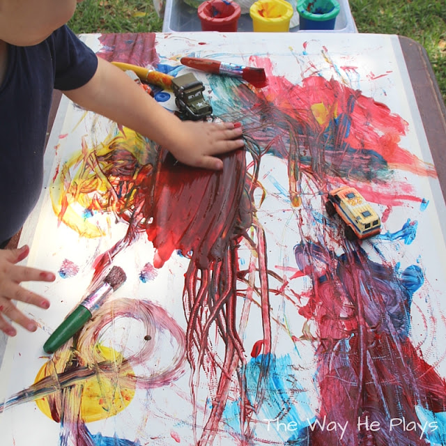 Toddler painting with his hands