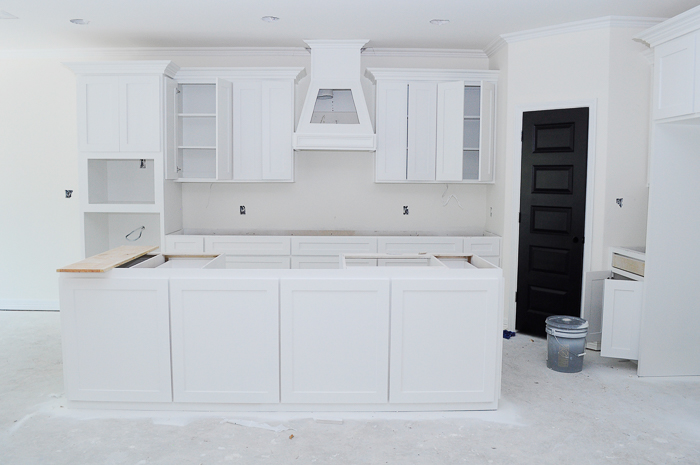 White kitchen with decorative vent hood and large island. Alabaster by Sherwin-Williams in a matte sheen for walls and tricorn black for door. | via monicawantsit.com