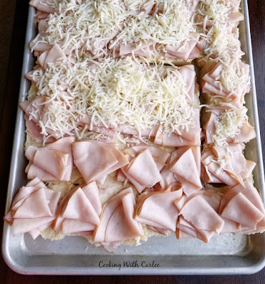 tray of partially assembled sliders with cheese, ham and turkey