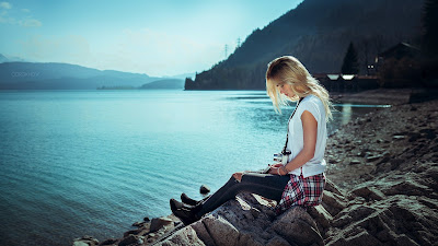 Chica con jeans negros sentada en piedra mirando al mar
