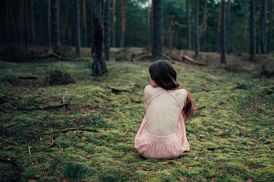Chica vestida de ballet sentada sola en pleno bosque
