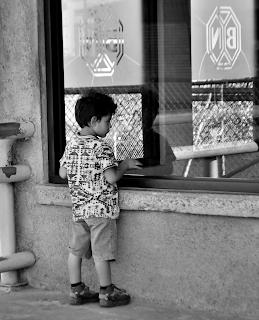 Boy watching people use the ATM machine at Banco Nacional
