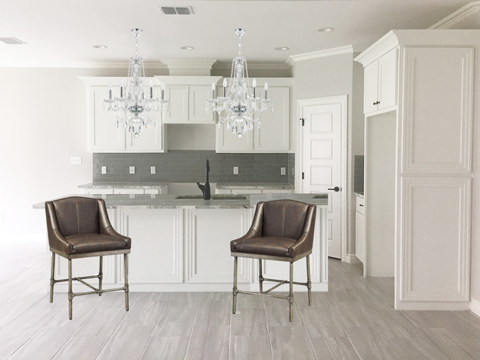 Double crystal chandeliers in a white shaker cabinet kitchen | via monicawantsit.com