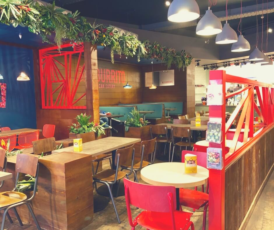 Inside the mexican eatery Barburrito. There are brown and red chairs dotted around square and round tables. There is also greenery in strategic places in the restaurant.