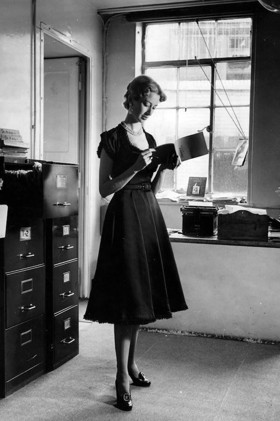 Published in 'Picture Post' with the original caption: 'A woman wearing a black satin dress by Brenner with baby lace around the sleeves, neck and hemline which is not really suitable for the office.' 1950.