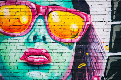 girl painted on wall - street art. Her skin is blue, she is wearing large orange sunglasses, and has purple hair