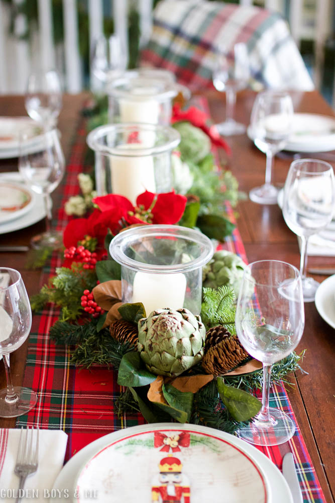 Classic Chrisrmas dining table setting with plaid runner, garland and fresh artichokes