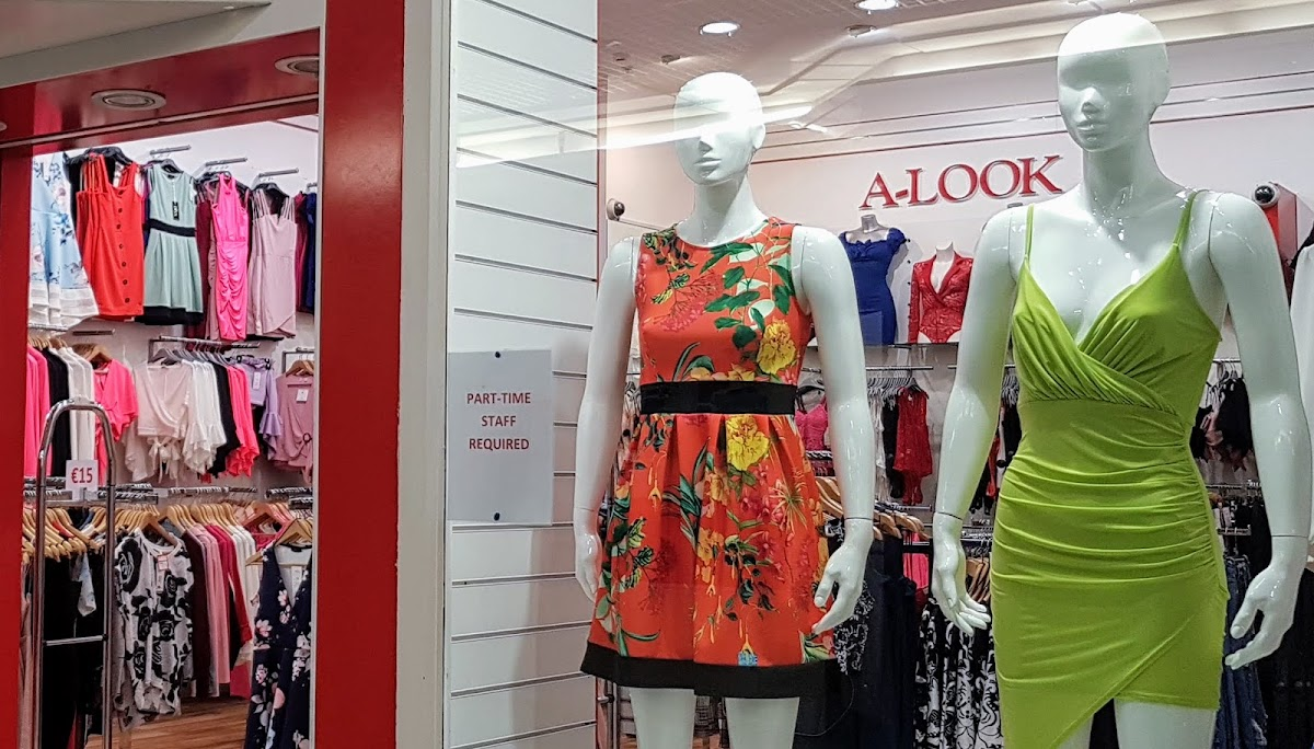 Shop window in a mall with two manequins wearing summer dresses in Irish colours