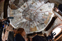 """People look at a fresco, part of the """"dei Fornai"""" (bakers) cubicle, during a visit after the restoration of the catacomb of Santa Domitilla, in central Rome, on May 30, 2017 [Credit: AFP/Andreas Solaro]"""