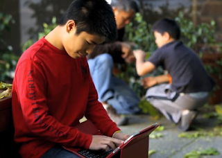 boy reading a tablet outside