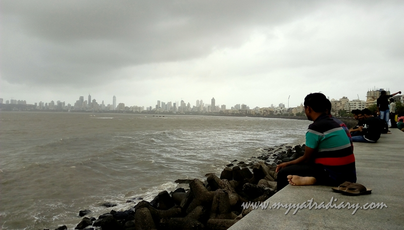 Two friends lost in conversation on the Marine Drive promenade, Mumbai