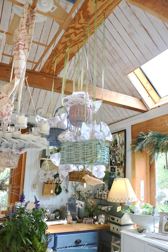 Spring baskets in pastel colors as ceiling display in the garden shed