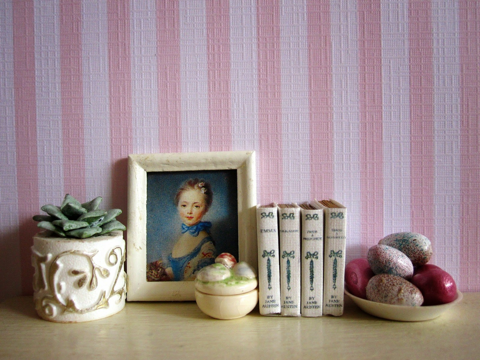 Modern miniature dolls' house scene with a white shelf in front of pink striped wallpaper. On the shelf is a succulent in a white and gold pot, a blue painting of a lady, a set of Jane Austen novels and a bowl of pink and white Easter eggs,