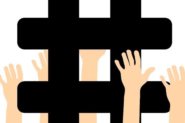 manos alzadas separadas por un hashtag que parece una reja de carcel