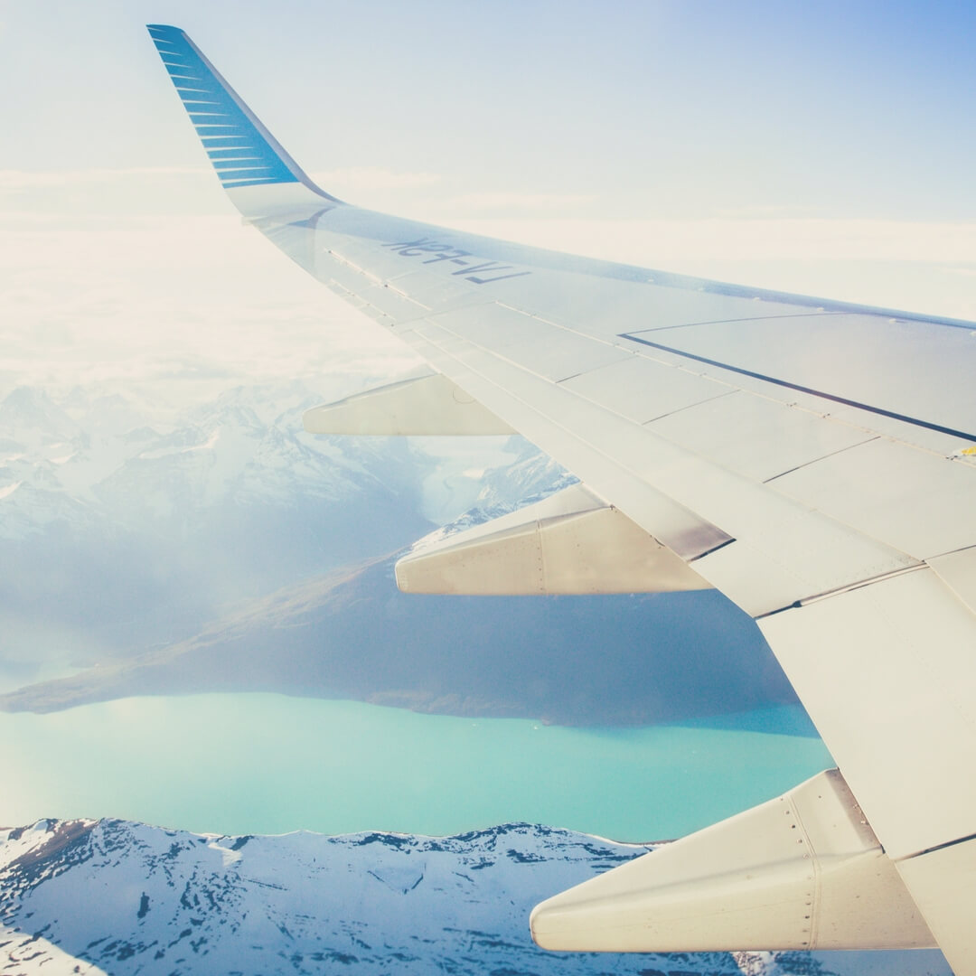 A plane's wing flying over snow-capped mountains, it is very sunny.