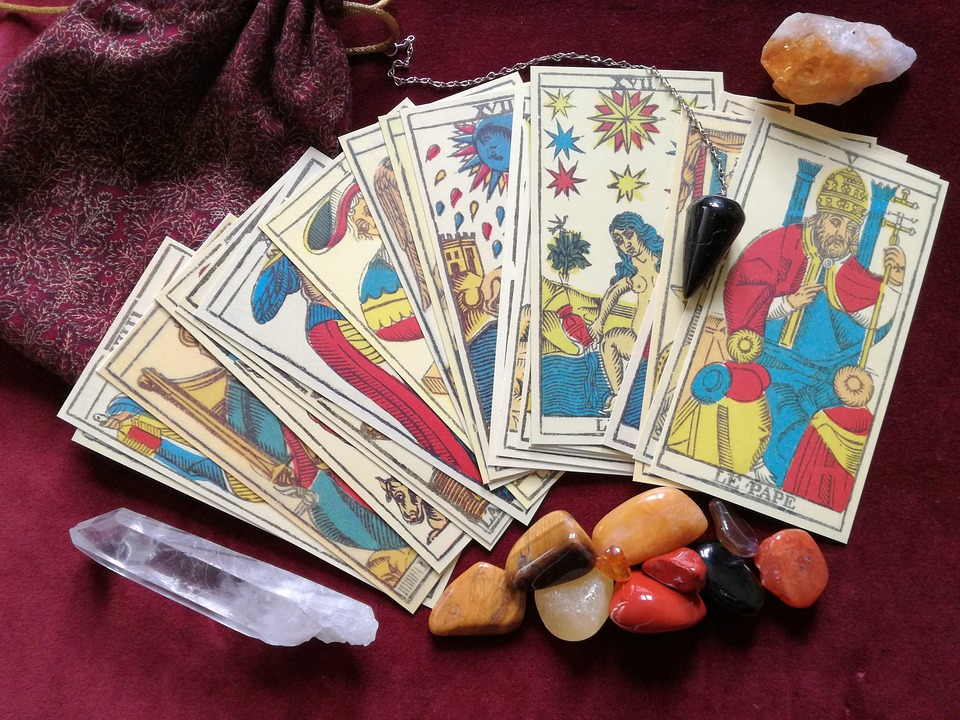 Hand holding Tarot Cards surrounded by crystals