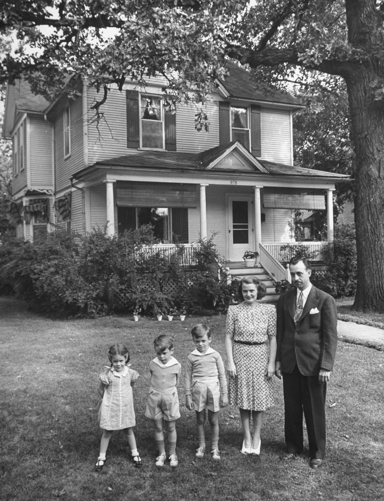 Jane posing with her husband of 11 years, Gilbert, and their three kids Pamela, 4, Tony, 5, and Peter, 7, in front of the large two-story house they lease.