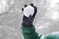 Bir çocuğun eldivenli elinde fırlatılmak üzere olan bir kartopu
