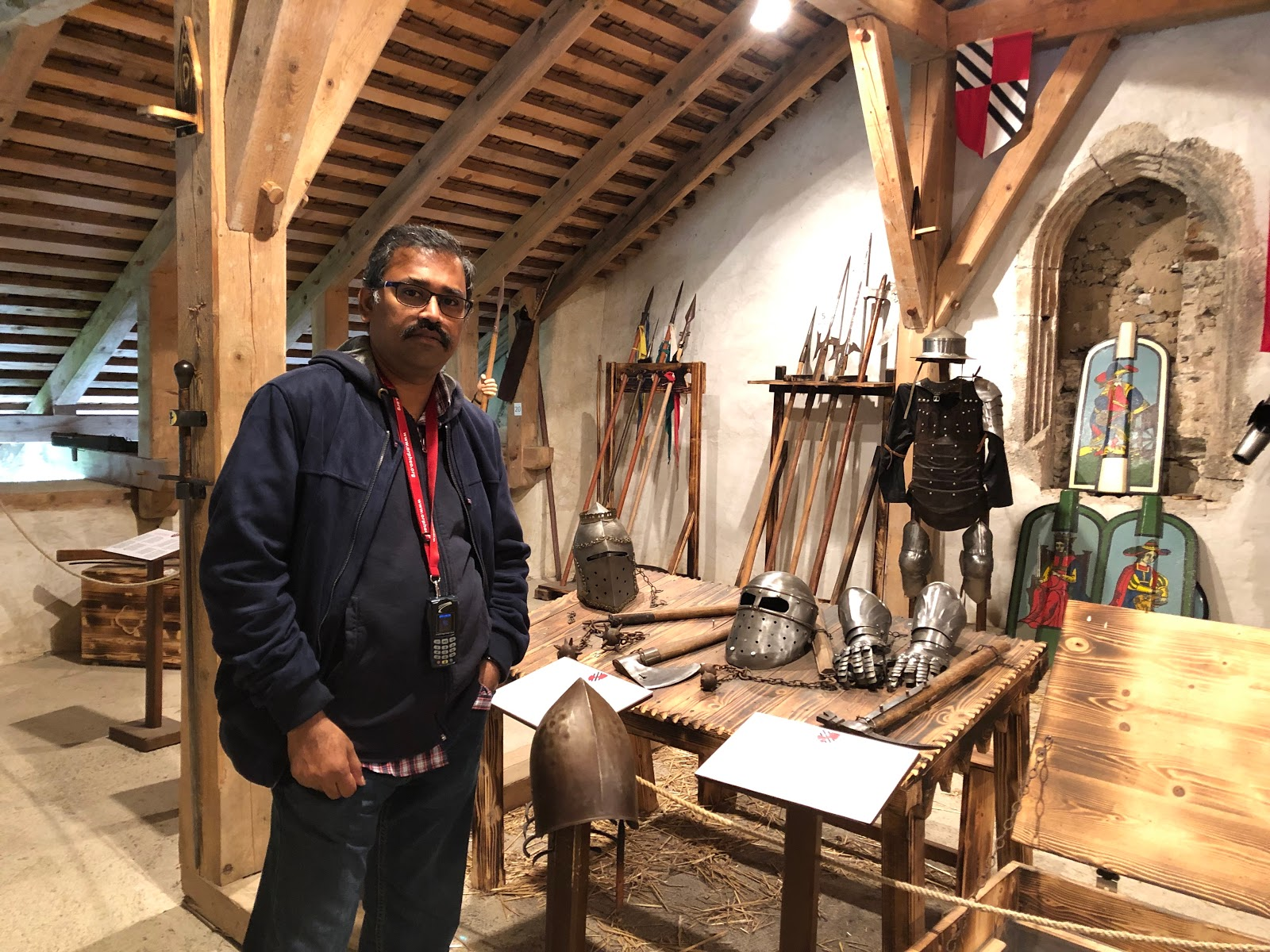 Man posing in front of the weapons and armours of the Knights in Predjama Castle.