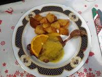 Plato de confit de pato con salsa de naranja y patatas fritas.
