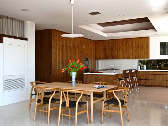 Picture of wooden dining table and chairs in the dining room and dark brown furniture in the kitchen with kitchen island