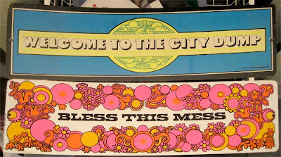 1970s-era signs in dayglow inks, Bless this Mess and Welcome to the City Dump