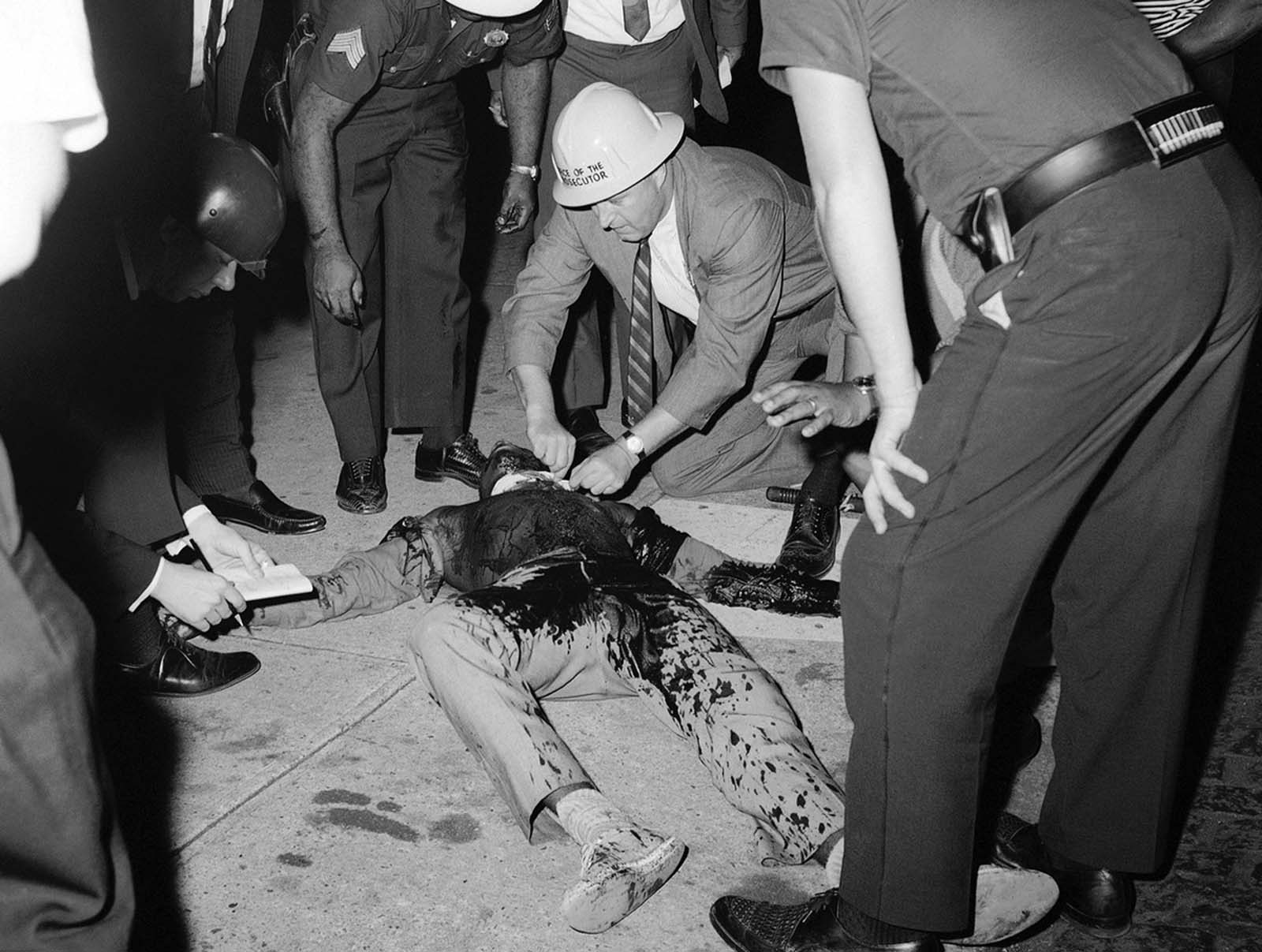 A black youth who was shot either in the neck or shoulder during a flare-up of racial violence in Jersey City, lies on a sidewalk while battle-helmeted policemen stand by to aid him on August 3, 1964. The youth, identified as Louis Mitchell, was among group of young people standing near a housing project who were hurling objects at the police. It was not determined how the youth was shot. At least one other resident was shot and several police officers and rioters were injured in the outburst.
