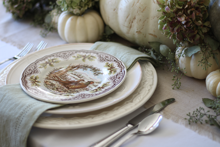 neutral fall tablescape with transferware plates and greens and creams