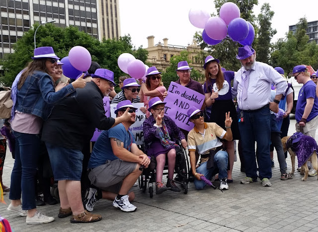 Kelly Vincent is in the centre sitting in a wheelchair surrounded by a group of approximately 15 people. The people either side of her are kneeling down and everyone else is standing in a semicircle around them. They are wearing purple fedora hats with white hatbands and leaning forward while giving hand gestures: either a thumbs up or a V for victory. Purple balloons are in the air. On the right hand side a guide or companion dog is wearing a purple glitter dog-coat. Everyone is looking to the right of the photograph where a photographer is taking a group portrait. In the background are plane trees and city buildings. A skyscraper on the left and a colonial sandstone treasury building on the right.