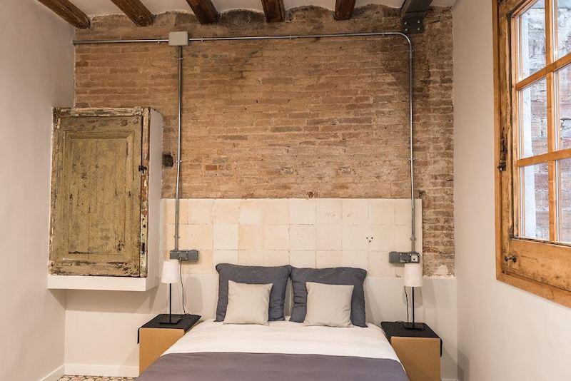 Dormitorio con cabecero de azulejos y mueble antiguo. Instalación de electricidad vista.