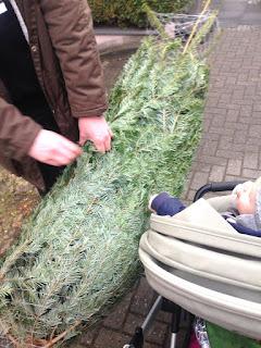 Der Mann und das Kind freuen sich über den noch verpackten Weihnachtsbaum und bringen ihn nach Hause